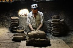 uyghur man at his workshop shaping traditional pottery stock photos
