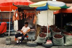 uyghur man selling meat and paprika spice at the local street market royalty free stock photography