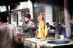 Uyghur Man warming hands Stock Image