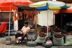 uyghur Mann, der Fleisch- und Paprikagewürz am lokalen Straßenmarkt verkauft lizenzfreie stockfotografie