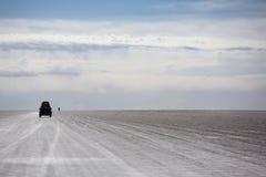 Uyuni撒拉族的全景与4x4汽车剪影,伯力的 免版税图库摄影