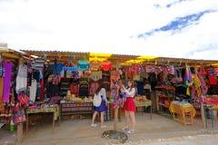 UYUNI,玻利维亚, 2018年1月31日:买纪念品的两个中国游人在平著名的盐,大众观光业, Uyuni附近 库存照片
