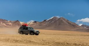 Uyuni, Bolívia, jipe no deserto com os vulcões no fundo fotografia de stock