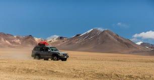 Uyuni, Bolivien, Jeep in der Wüste mit den Vulkanen im Hintergrund stockfotografie
