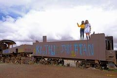 Uyuni, Boliwia, Styczeń 31, 2018: Dwa chińskiego turysty stoi na ośniedziałym pociągu przy taborowym cmentarzem, masowa turystyka obrazy stock