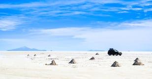 Uyuni Salt desert, Bolivia. Piles of salt to dry in the Bolivian desert and car Royalty Free Stock Image