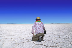 Uyuni salt lake traveler. Traveler with straw hat and scarf in bolivian national colors kneels at the desert of Uyuni, Bolivia and looks at the wideness of the Royalty Free Stock Photos