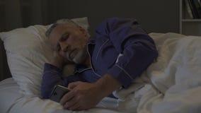 Uzależniający się smartphone starszego mężczyzna scrolling zastosowanie zamiast dosypiania zbiory wideo