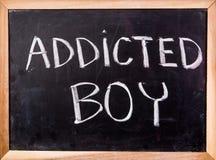 Uzależniony chłopiec słowo na blackboard zdjęcia royalty free