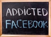 Uzależniony facebook słowo na blackboard fotografia royalty free