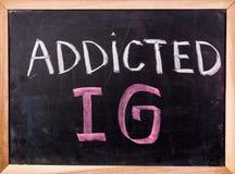 Uzależniony IG słowo na blackboard fotografia stock