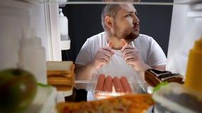 Uzależniony mężczyzna skrycie je kiełbasy przy nocą blisko fridge, niezdrowy odżywianie fotografia stock