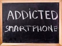 Uzależniony smartphone słowo na blackboard obraz stock