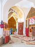 The Uzbek bazaar. BUKHARA, UZBEKISTAN - APRIL 28, 2015: The interior of the Telpak Furushon Trading Dome with numerous carpets and embroidered tableclothes Stock Images