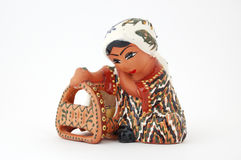 Uzbek Ceramic Figurine. Isolated photo of traditional Uzbek ceramic figurine of a young mother rocking a baby crib Stock Images