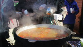 Uzbek cuisine, the chef prepares a dish liquid. The Uzbek national clothes cook prepares a tasty liquid dish in a large pan over a fire which produces steam stock video footage