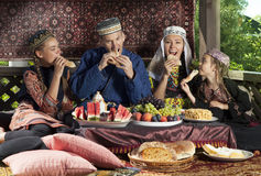 Uzbek family have breakfast with flat cakes Stock Photography