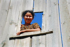 Uzbek girl looking down a wooden fence Royalty Free Stock Photos
