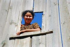 Uzbek girl looking down a wooden fence Royalty Free Stock Photos