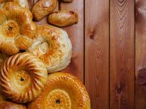 Uzbek national bread on wooden table on dark background Royalty Free Stock Images