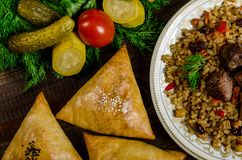 Uzbek National Dish Of Pilaf And Samsa On A Dark Wooden Background With Pickles Stock Photo