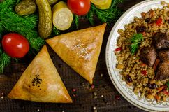 Uzbek National Dish Of Pilaf And Samsa On A Dark Wooden Background With Pickles Royalty Free Stock Photography