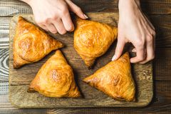 Uzbek national dish of samsa on a wooden board in the hands of a girl Royalty Free Stock Photography