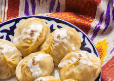 Uzbek national food manti on traditional fabric adras Stock Photos