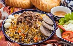 Uzbek national food pilaf on traditional fabric adras Stock Photography