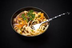 Uzbek noodle soup Lagman on black Royalty Free Stock Photos