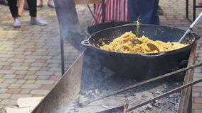 Uzbek pilaf is cooked in a cauldron over a fire on street stock footage