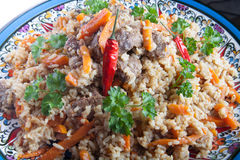 Uzbek pilaf in a dish with hot peppers and fresh cilantro Stock Image