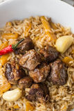 Uzbek Pilaf - Rice with Meat and Vegetables on the table. Pilaf with lamb and garlic zira. close up.  Royalty Free Stock Photo