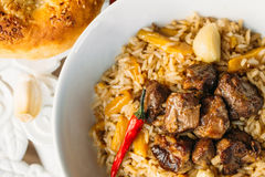 Uzbek Pilaf - Rice with Meat and Vegetables on the table. Pilaf with lamb and garlic zira. close up Stock Photo
