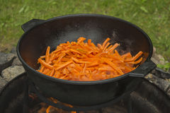 Uzbek rice pilaf cooking process. Carrot in cauldron. Royalty Free Stock Images