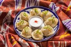 Uzbeka krajowy karmowy manti na tradycyjnych tkanin adras Fotografia Stock