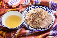 Uzbeka krajowy karmowy norin na tradycyjnych tkanin adras Zdjęcie Stock