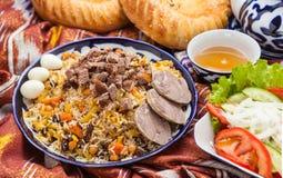 Uzbeka krajowy karmowy pilaf na tradycyjnych tkanin adras Fotografia Stock