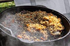 Uzbekisk pilaff lagas mat i en kittel på mässan arkivfoto