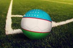 Uzbekistan ball on corner kick position, soccer field background. National football theme on green grass.  royalty free illustration