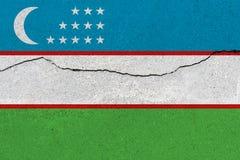 Uzbekistan flag on concrete wall with crack. Patriotic grunge background. National flag of Uzbekistan royalty free stock photo
