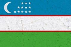 Uzbekistan flag on concrete wall. Patriotic grunge background. National flag of Uzbekistan stock images