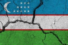 Uzbekistan flag on the cracked earth. National flag of Uzbekistan. Earthquake or drought concept stock photos