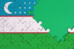 Uzbekistan flag is depicted on a completed jigsaw puzzle with free green copy space on the right side.  royalty free stock images