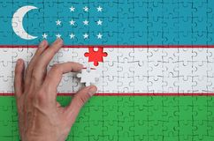Uzbekistan flag is depicted on a puzzle, which the man`s hand completes to fold.  stock image