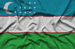 Uzbekistan flag is depicted on a sports cloth fabric with many folds. Sport team banner. Uzbekistan flag is depicted on a sports cloth fabric with many folds stock photography