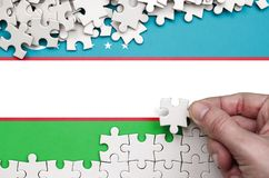 Uzbekistan flag is depicted on a table on which the human hand folds a puzzle of white color.  stock photos