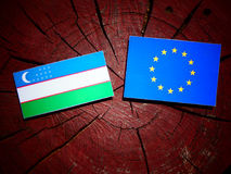 Uzbekistan flag with EU flag on a tree stump isolated Royalty Free Stock Photography