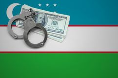 Uzbekistan flag with handcuffs and a bundle of dollars. The concept of breaking the law and thieves crimes.  royalty free stock photos