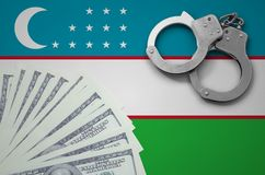 Uzbekistan flag with handcuffs and a bundle of dollars. The concept of illegal banking operations in US currency.  royalty free stock image